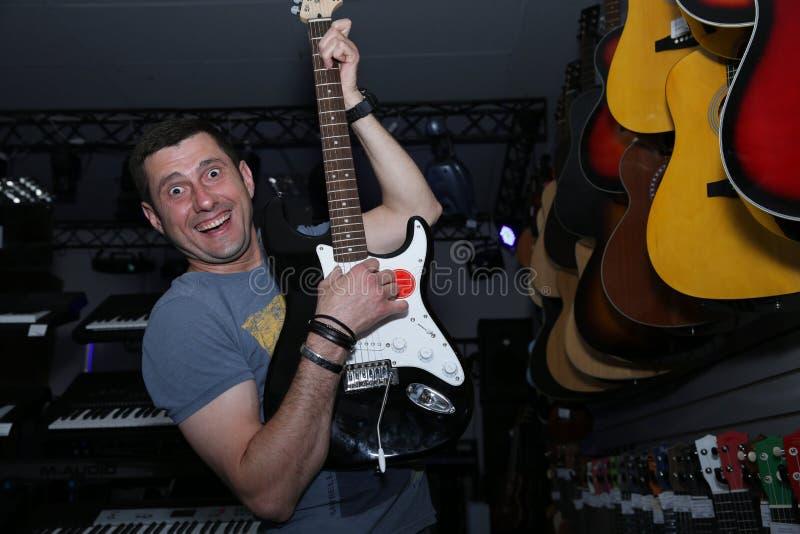 活跃情感与在他的面孔的微笑弹一把电吉他的年轻人以在软的迷离的吉他为背景 图库摄影