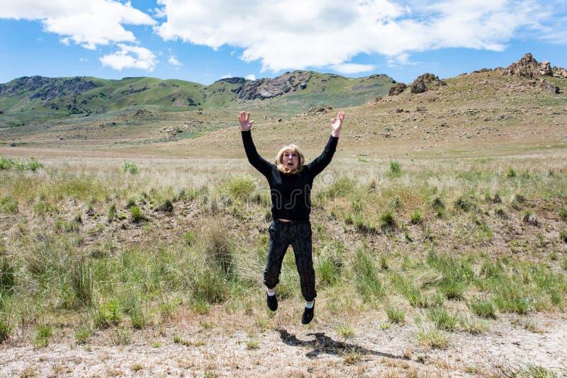 活跃资深妇女为喜悦跳在一个草甸在羚羊海岛国家公园 库存图片