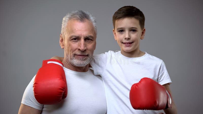 活跃资深男性和男孩看对照相机,健康生活方式的拳击手套的 库存图片