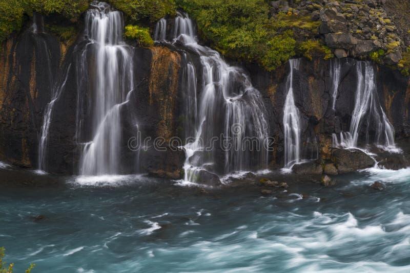流入蓝色河的瀑布 图库摄影