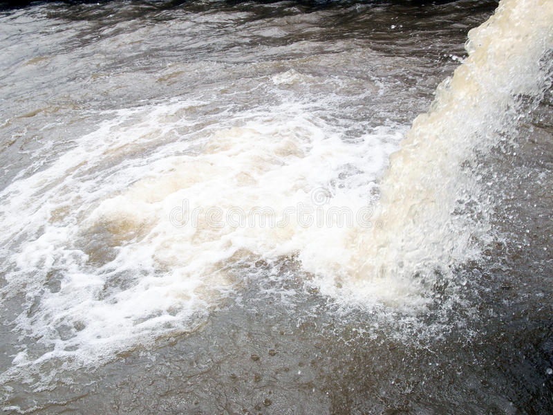 流出从工业工厂输送管道浇灌到河 库存照片