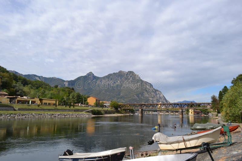 流动从湖科莫湖,渔夫和汽艇的阿达河河停住在岸 免版税库存图片