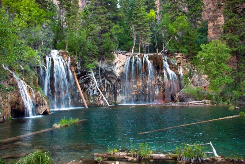 流动入山池塘的山瀑布 免版税库存照片