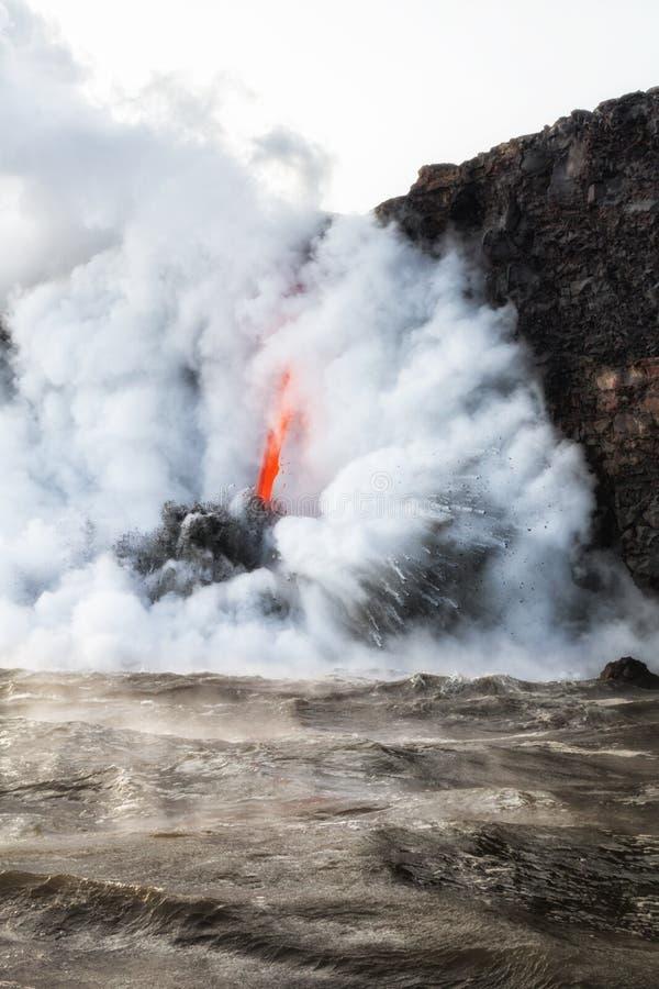 流动入有蒸汽和烟的海洋的熔岩 免版税库存图片