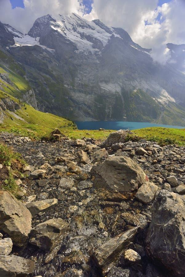流动到湖的小河 Oeschinensee, Kandersteg 伯纳Oberland 瑞士 免版税库存图片