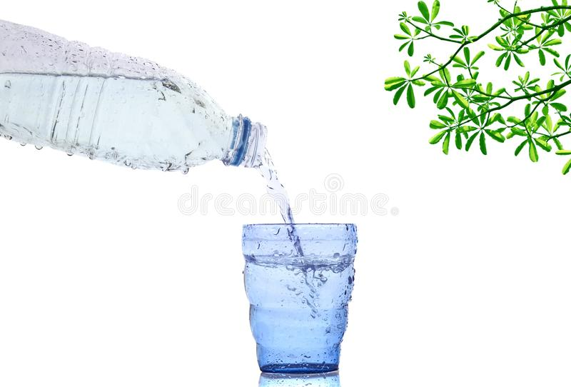 流动到蓝色玻璃的凉快的新鲜的饮用水瓶 免版税库存照片
