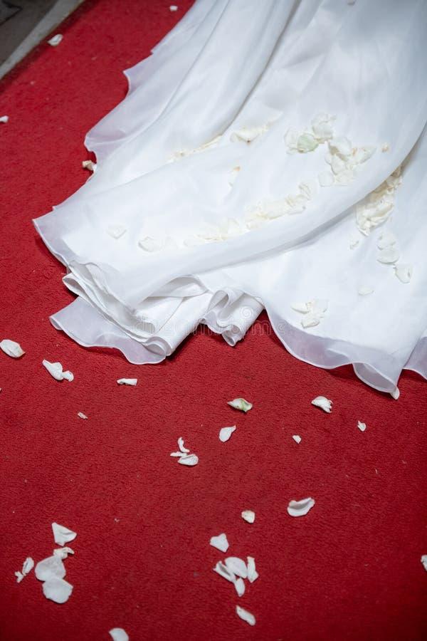 流动到隆重的地板背景的一部分的白色新娘婚纱足迹褂子 库存照片