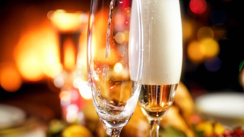 流动在两块玻璃中的香槟的特写镜头图象反对灼烧的壁炉 免版税库存图片