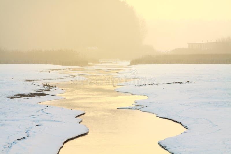 流动在冬天的小小河在日出期间 免版税库存照片