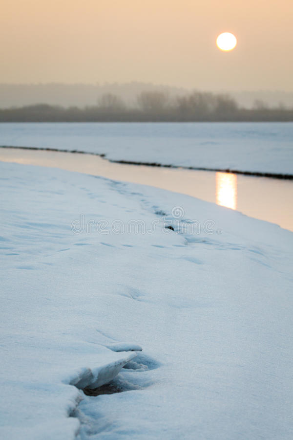 流动在冬天的小小河在日出期间 免版税库存图片