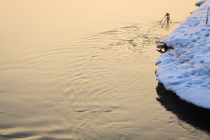 流动在冬天的小小河在日出期间 图库摄影