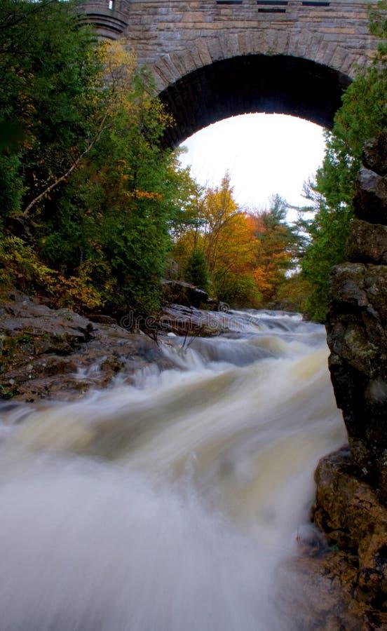 流动在历史的被成拱形的石桥梁阿卡迪亚国民下的河 库存照片