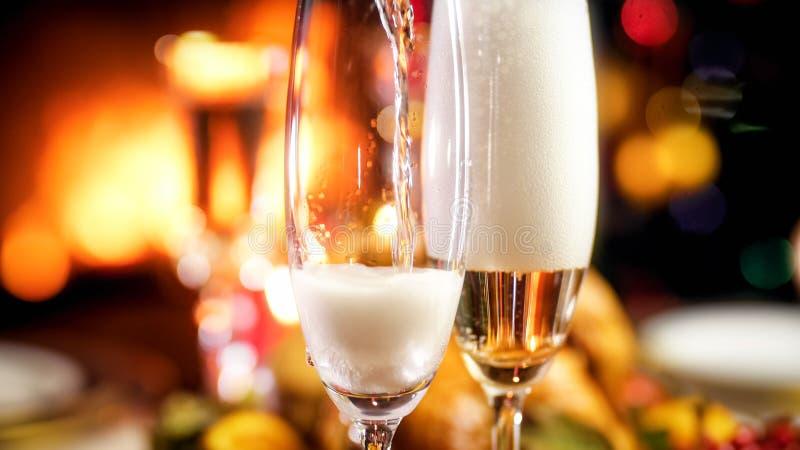 流动在浪漫晚餐的玻璃的香槟的特写镜头图象在壁炉 免版税图库摄影