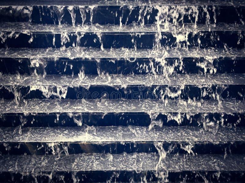 流动在黑台阶步下的凉水 库存图片