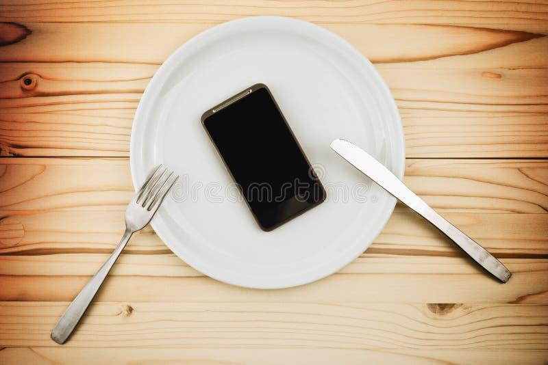 流动巧妙的电话担当了在白色板材的晚餐 库存照片