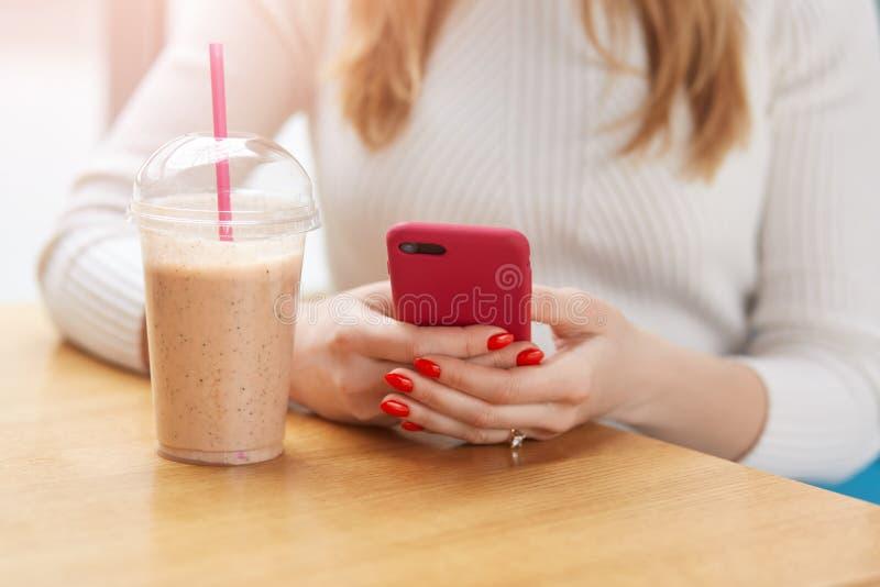 流动智能手机在有明亮的红色修指甲的白肤金发的女性手上,在桌上把胳膊放在鸡尾酒附近,找到在小配件的信息 库存照片