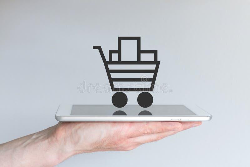流动网上购物的概念 拿着片剂或大巧妙的电话的手 免版税库存图片