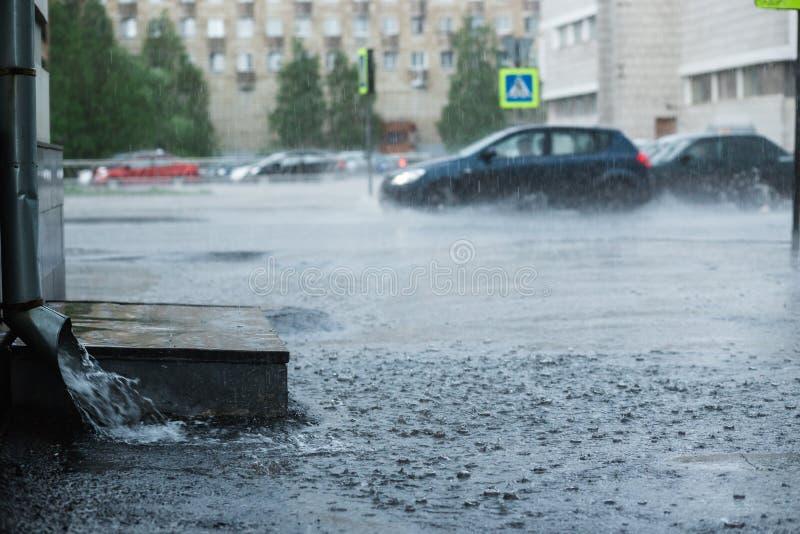 流动从金属水落管的雨水在大雨期间 的概念防护大雨和雨洪水 免版税图库摄影