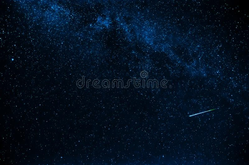 流星在背景中满天星斗的蓝色黑暗的天空 库存照片