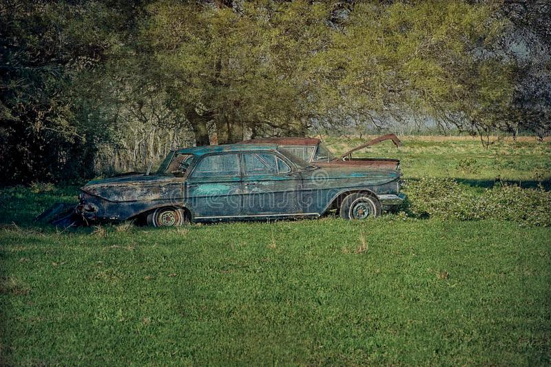 流浪汉被放弃的古董车在开放草甸 免版税库存图片