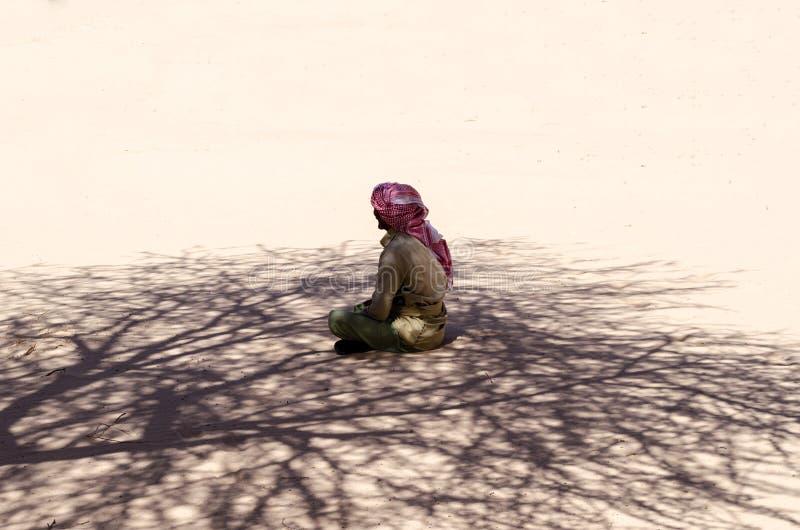 流浪者在沙子在一棵树的树荫下坐并且祈祷在沙漠在埃及宰海卜南西奈 库存照片