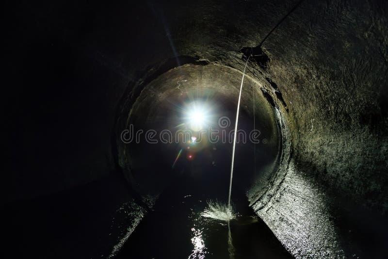 流经排水设备回合下水道隧道管子的肮脏的污水 库存照片