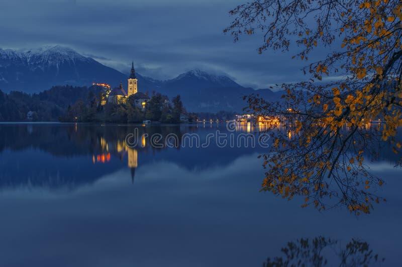流血的湖和朝圣教会微明的在水中反射了 库存照片
