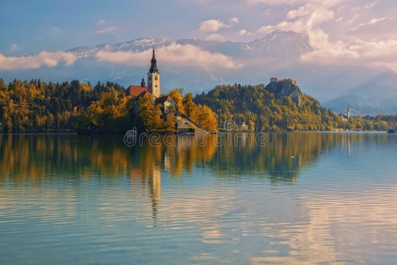 流血的湖和朝圣教会有秋天山风景背景 库存图片