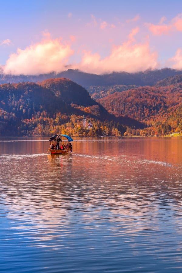 流血的,斯洛文尼亚小船和教会日落的 免版税库存照片