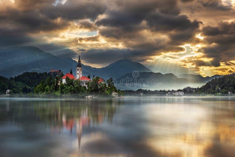 流血,斯洛文尼亚-在布莱德湖与玛丽亚的做法的朝圣教会的Blejsko Jezero的令人惊讶的金黄日出 免版税库存图片