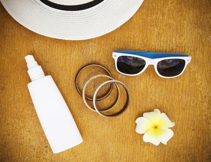 流行的服装太阳镜,时髦的镯子,帽子,奶油色fo 免版税图库摄影