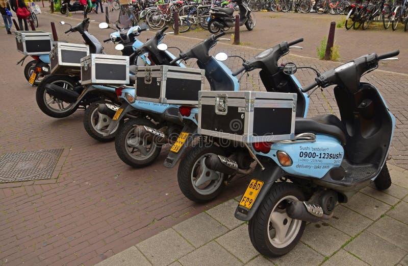 浅兰的交付摩托车在阿姆斯特丹连续一起停放了 库存图片