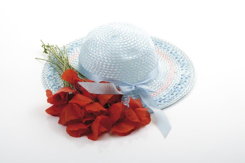 浅兰的少女夏天帽子和一束鸦片 免版税库存图片