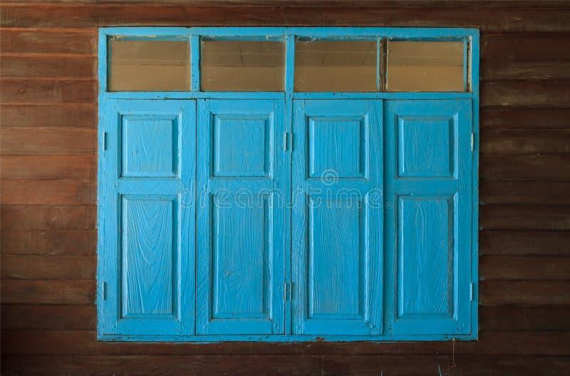 浅兰的被绘的葡萄酒减速火箭的木窗口和单块玻璃,反对简单的热带黑褐色的家内部建筑设计 库存图片