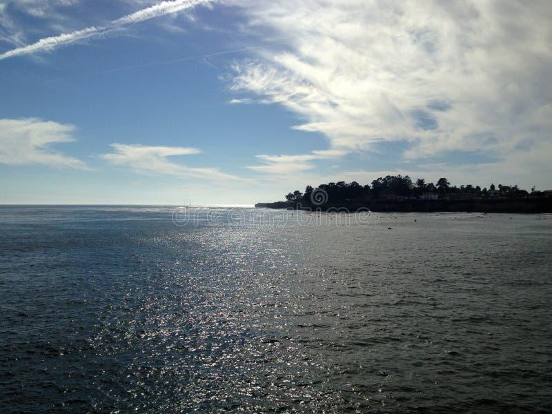 浅兰的水海和海岛海洋的沿岸航行在蓝天下与白色云彩 库存照片