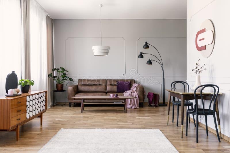 浅灰色的客厅内部真正的照片与窗口与帷幕,皮革长沙发,与两把椅子地毯的桌的在木flo 免版税图库摄影