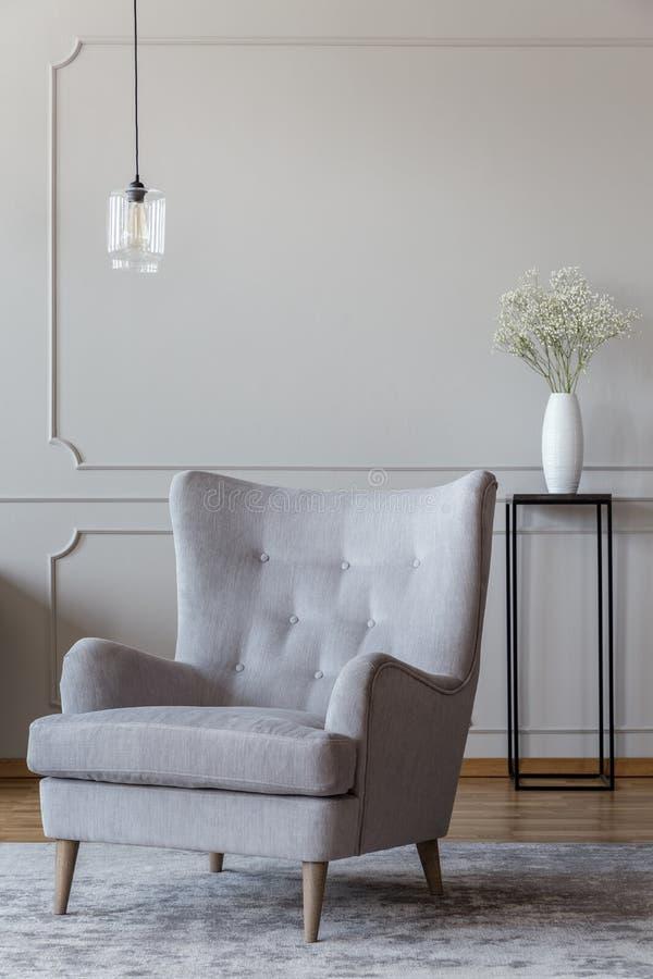 浅灰色,典雅的站立在soph的扶手椅子和一个黑花瓶 免版税库存图片