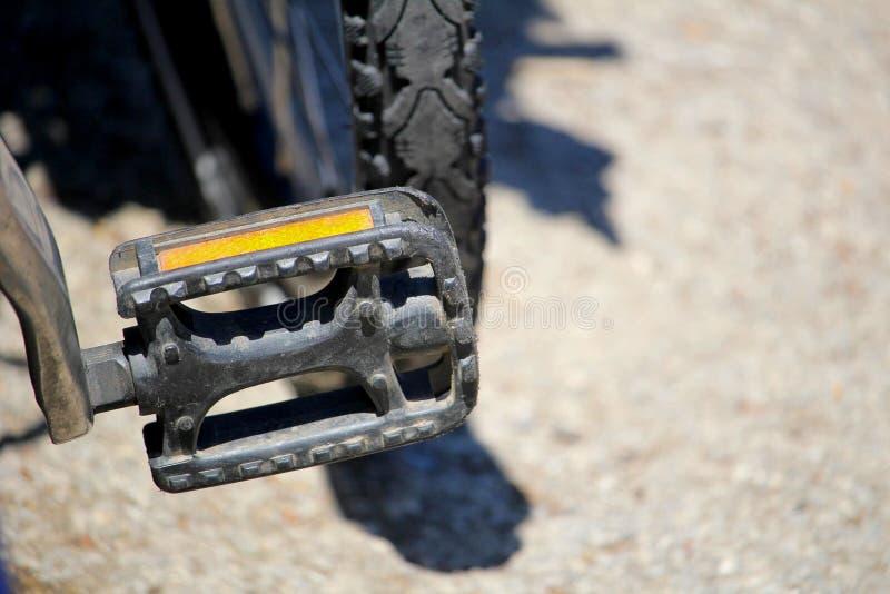 浅焦点关闭脚蹬和橙色反射器在自行车 免版税库存图片