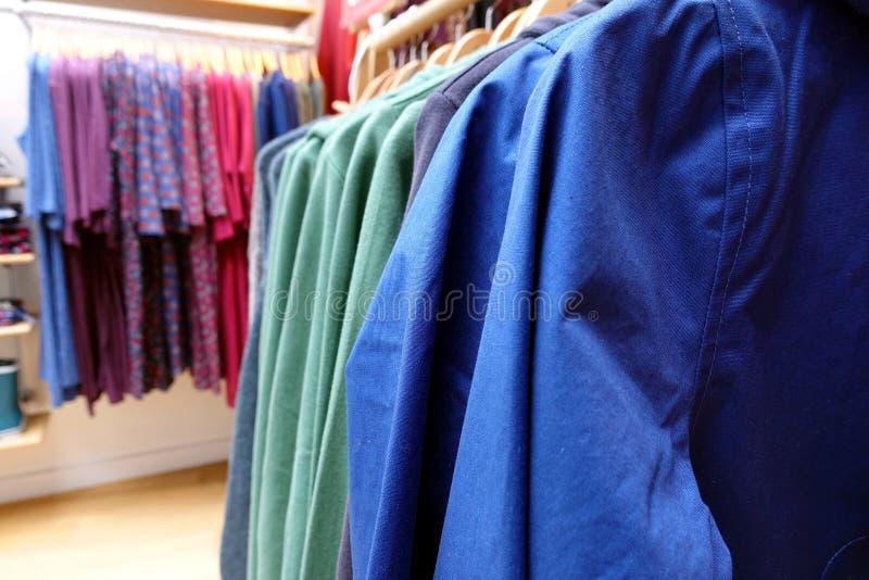 浅焦点关闭蓝色和绿色衣裳机架在a的 图库摄影