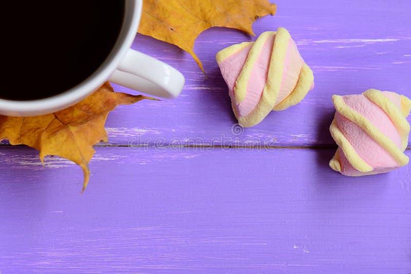 浅粉红色和黄色蛋白软糖,黄色秋叶,在紫色木背景的咖啡杯 容易的秋天咖啡休息 库存图片