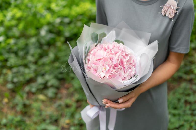 浅粉红色的八仙花属 举行花的布置的女孩 美丽的夏天花束 花店的概念 图库摄影