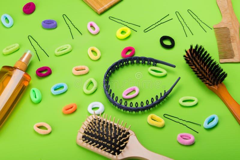 浅绿色的背景、疏散对象创造发型的,不同的颜色橡皮筋和一把梳子和一朵浪花styl的 库存照片