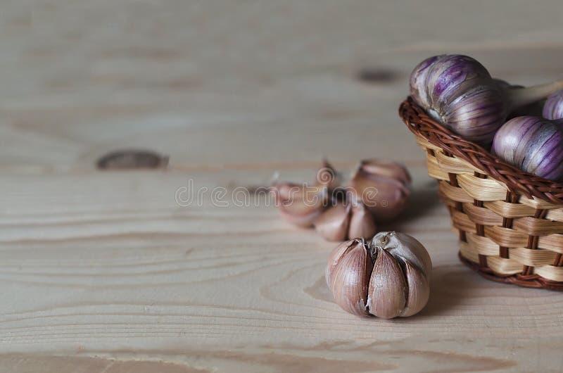 浅色木质背景上的木制柳条篮中的大蒜球茎、大蒜头、单个丁香 辣辣 免版税库存照片