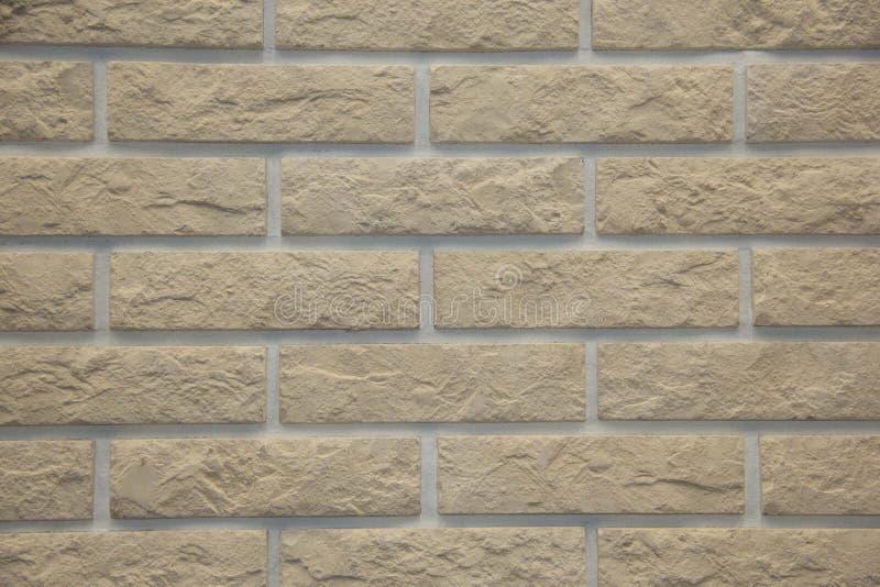 浅褐色的在强调石头纹理和深度的坚硬光的石头砖外墙 免版税库存照片