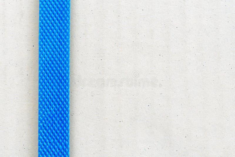 浅褐色的纸板箱/小包紧固了与蓝色塑料/尼龙皮带在运输对几个区域前 免版税库存照片