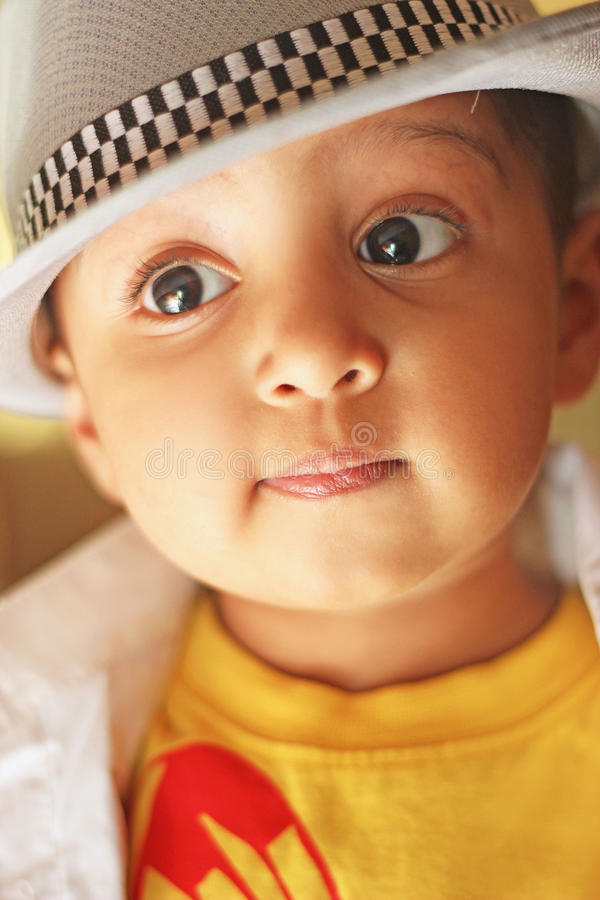 戴浅顶软呢帽帽子的一个逗人喜爱的南亚男孩的画象 库存图片