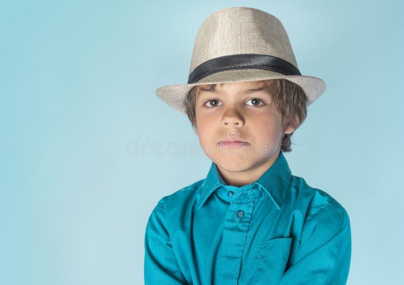 浅顶软呢帽的小男孩与严肃的表示 免版税图库摄影