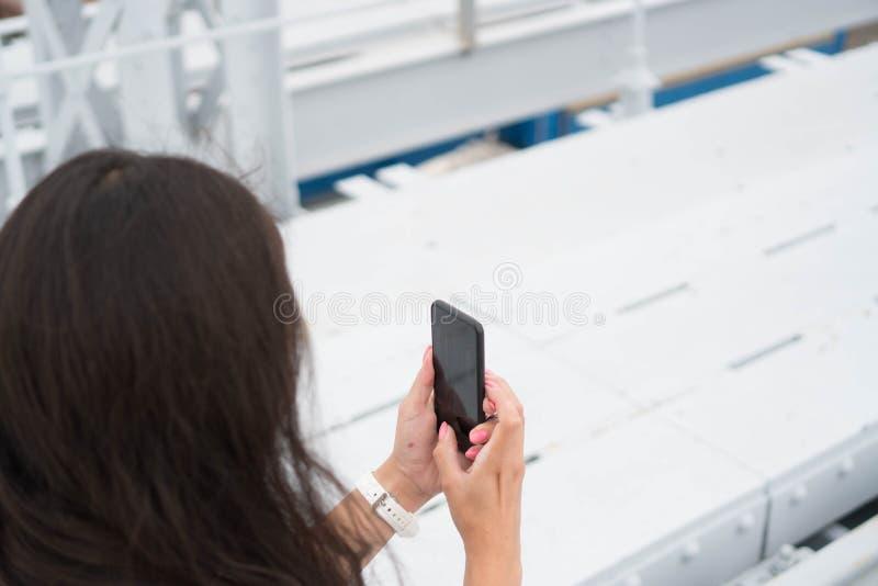 浅黑肤色的男人拿着电话用两只手,照片视域 长发女孩游人拍照片,从后面的图片, 库存图片