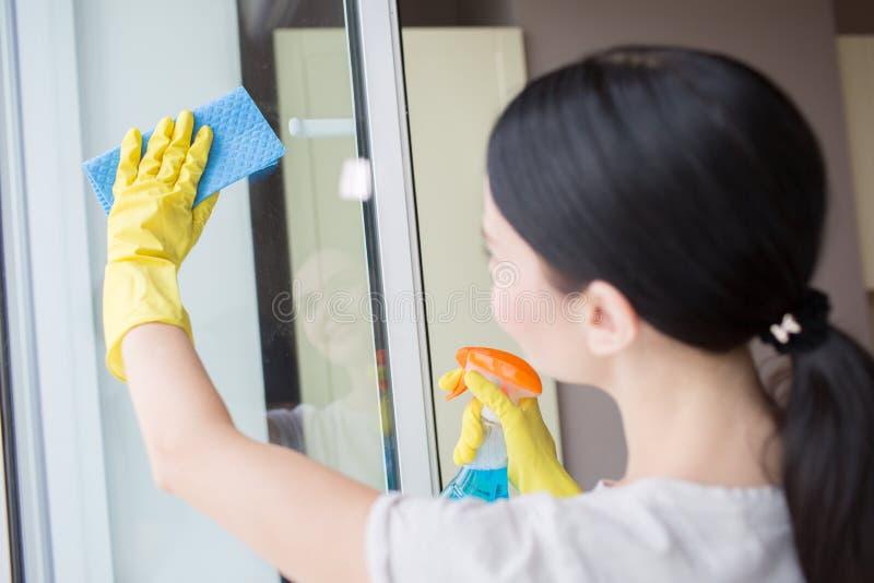 浅黑肤色的男人清洗杯窗口与蓝色旧布和液体浪花 她做它仔细 免版税库存照片