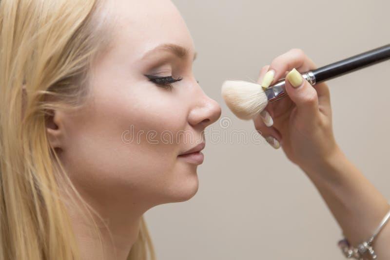 浅黑肤色的男人组成申请艺术家的妇女补偿一白肤金发的brid 免版税图库摄影